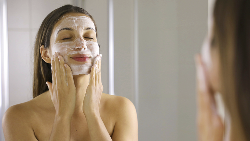 Mujer aplicándose un facial en casa