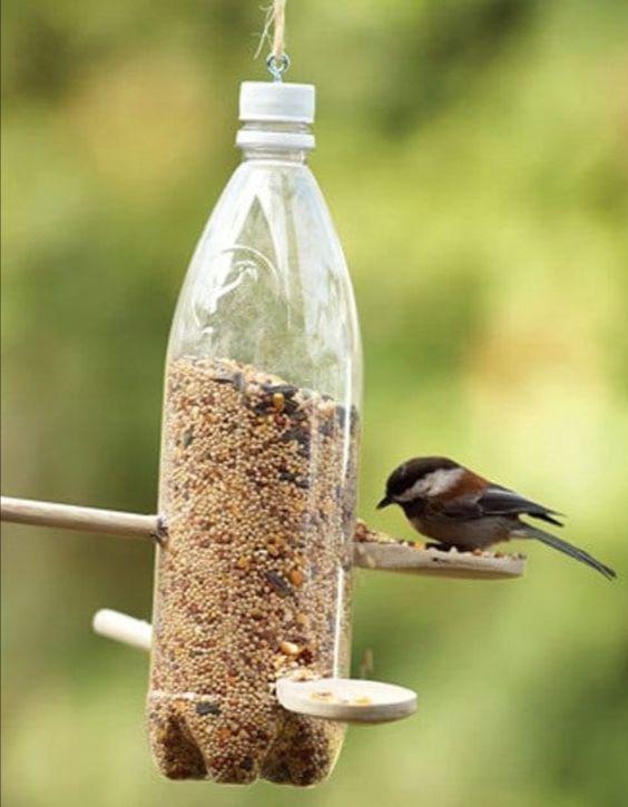 Bote de plástico con comida para pájaros