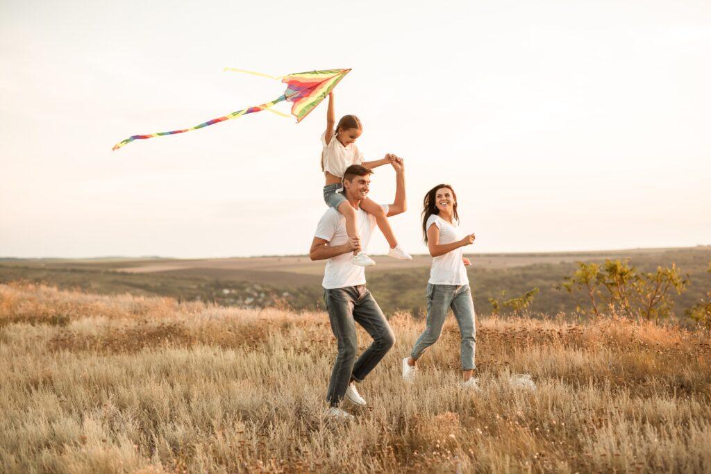 Padres e hija en el campo volando un cometa