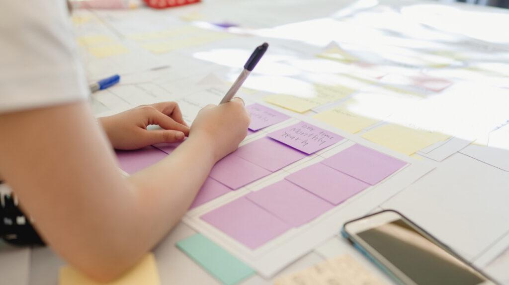 Persona organizando su plan de trabajo con post Its para tener un día productivo