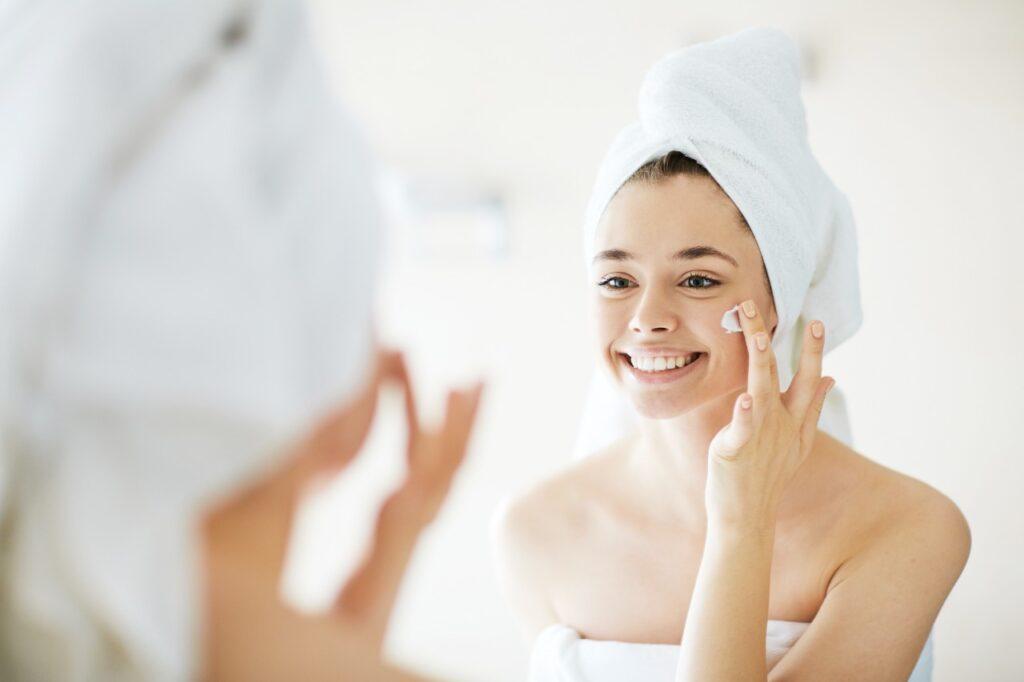 Mujer de piel grasa aplicándose crema en el rostro