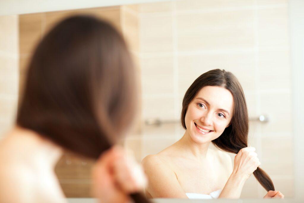 Mujer admirando su cabello en el espejo